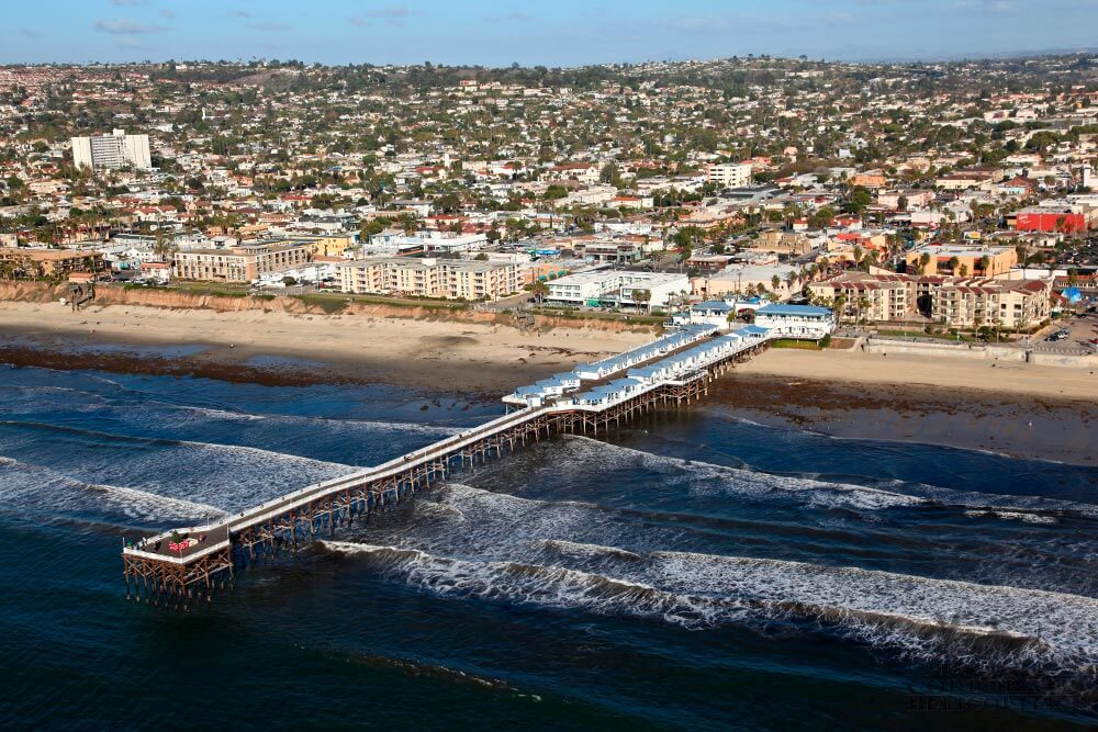 Helicopter tour from Corporate Helicopters of San Diego. Helicopter flying over Crystal Pier in Pacific Beach.